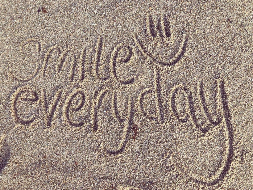 Smile everyday written in the sand